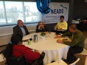 In this image, there are five adults conversing around a table with the NEADS banner behind one individual.