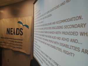 To the left is an image of a white banner with the NEADS logo and text describing disability - Image depicting conference banner at the Breaking it Down Events.